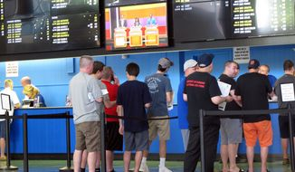 In this June 19, 2018, file photo, sports bettors line up at windows at Monmouth Park racetrack in Oceanport, N.J. With the legalization of sports gambling in the United States and its gradually expanding implantation, some in the industry are suggesting horse racing add fixed-odds wagering as a way to respond to the changing landscape, evolve and compete with the other options now available. (AP Photo/Wayne Parry, File) **FILE**
