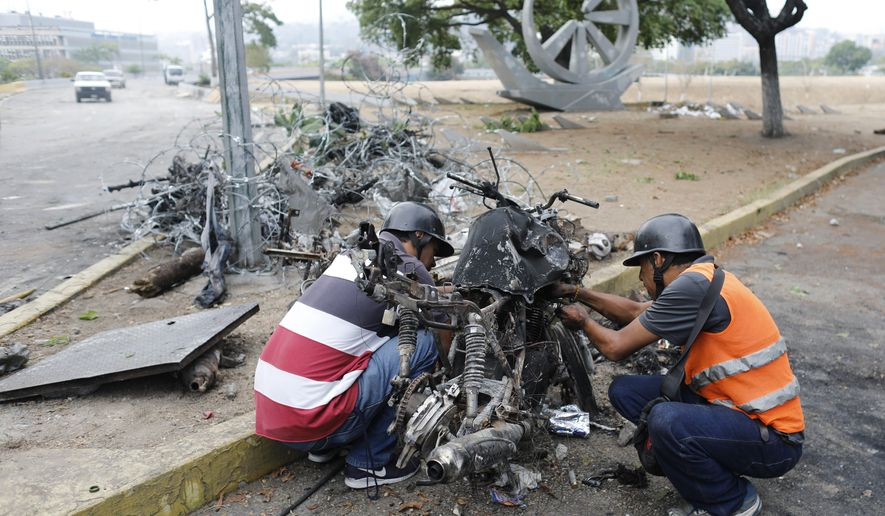 Men look to recover usable parts from motorcycles burned during the previous day's clashes between anti-government protesters and security forces near La Carlota airbase in the Altamira neighborhood of Caracas, Venezuela, Wednesday, May 1, 2019. Venezuela's capital is awakening to a tense calm as the country prepares for a new round of protests after a dramatic day of political upheaval, with opposition leader Juan Guaido calling for Venezuelans to fill streets around the country to demand President Nicolas Maduro's ouster. (AP Photo/Ariana Cubillos)