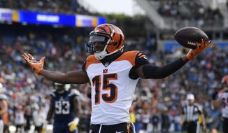 FILE - In this Dec. 9, 2018, file photo, Cincinnati Bengals wide receiver John Ross (15) celebrates after scoring a touchdown against the Los Angeles Chargers during the first half of an NFL football game in Carson, Calif. Receiver John Ross read reports that the Bengals were going to trade him during the draft. Not only did they keep him, they chose not to get any more receivers, leaving Ross with an important role. (AP Photo/Mark J. Terrill, File)