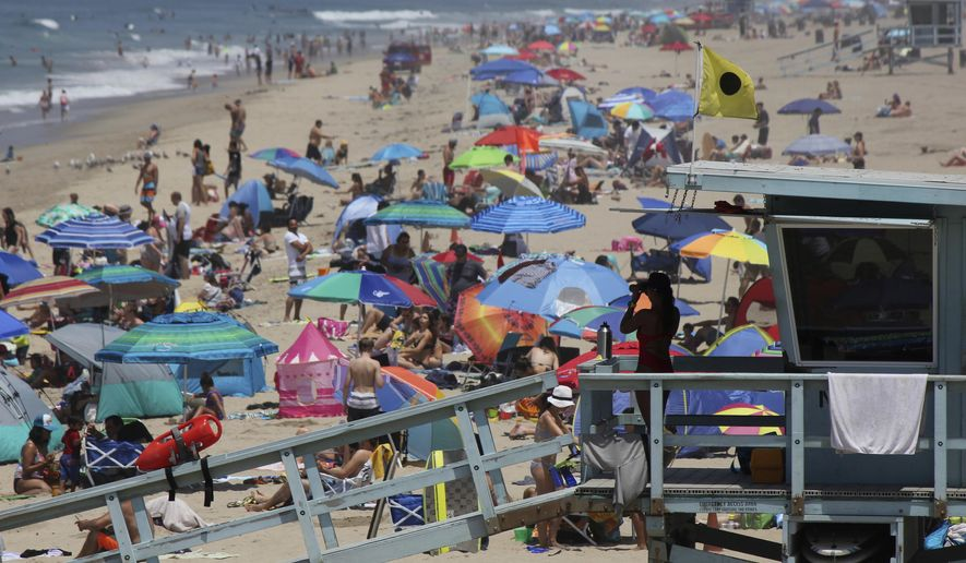 FILE - In this July 8, 2017 file photo a lifeguard scans a crowded shoreline at Manhattan Beach, Calif. New population estimates show California's births fell by 18,000 last year, prompting the slowest recorded growth rate in the country's most populous state. (AP Photo/John Antczak,File)