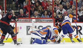 Carolina Hurricanes' Teuvo Teravainen, right, of Finland, scores against New York Islanders goalie Robin Lehner (40), of Sweden, while Islanders Anders Lee defends at right during the first period of Game 3 of an NHL hockey second-round playoff series in Raleigh, N.C., Wednesday, May 1, 2019. (AP Photo/Gerry Broome)