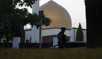 FILE - In this March 17, 2019, file photo, a police officer stands guard in front of the Al Noor mosque in Christchurch, New Zealand. New Zealand's major media organizations pledged Wednesday, May 1, 2019, not to promote white supremacist ideology when covering the trial of the man charged with killing 50 people at two mosques.(AP Photo/Vincent Yu, File)