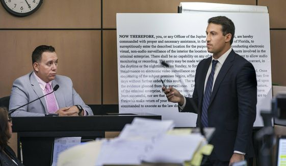 Alex Spiro, right, attorney for New England Patriots owner Robert Kraft, stands in front of a copy of a search warrant as he questions Jupiter Police Detective Andrew Sharp during a motion hearing in the Kraft prostitution solicitation case, Wednesday, May 1, 2019, in West Palm Beach, Fla. Kraft's attorneys argue that undercover surveillance videos allegedly showing their client paying for sex at a Jupiter day spa should be ruled inadmissible and the evidence thrown out. (Lannis Waters/Palm Beach Post via AP, Pool)