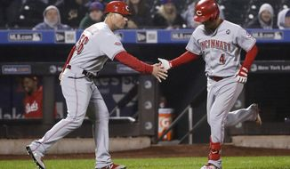 Cincinnati Reds' Jose Iglesias, right, celebrates with third base coach J.R. House after hitting a home run during the ninth inning of the team's baseball game against the New York Mets on Wednesday, May 1, 2019, in New York. The Reds won 1-0. (AP Photo/Frank Franklin II)