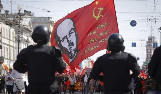 Communist party supporters carry a flag depicting Soviet Union founder Lenin during a May Day rally in St.Petersburg, Russia, Wednesday, May 1, 2019. (AP Photo/Dmitri Lovetsky) **FILE**