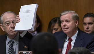 Senate Judiciary Committee Chairman Lindsey Graham, R-S.C., right, joined at left by Sen. Chuck Grassley, R-Iowa, raises a copy of Mueller report, during his opening statement before swearing-in Attorney General William Barr to testify, on Capitol Hill in Washington, Wednesday, May 1, 2019. (AP Photo/J. Scott Applewhite)