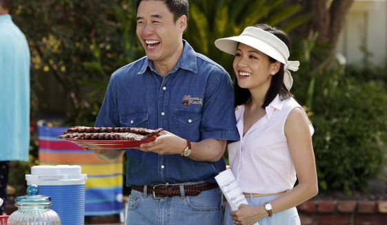 """In this image released by ABC, Randall Park, left, and Constance Wu appear in a scene from the new comedy series """"Fresh Off the Boat."""" The Asian Pacific American Media Coalition released its report card for the big four networks Wednesday, May 1, 2019, the first day of Asian Pacific American Heritage Month. Of all the networks, ABC was ahead of the class. (Nicole Wilder/ABC via AP)"""