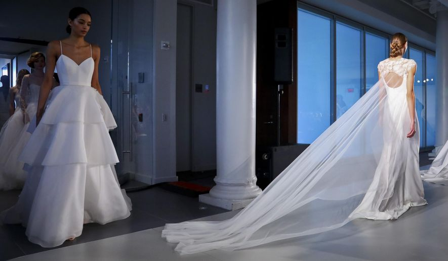 FILE - This April 12, 2019 file photo shows fashion from the Amsale bridal collection in New York. Bridal sites TheKnot.com, WeddingWire.com and Spanish-language Bodas.net released a report on wedding trends and traditions worldwide. (AP Photo/Bebeto Matthews, File)