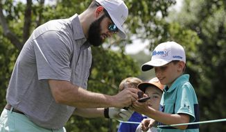 Carolina Panthers draft pick Will Grier wtakes signs an autograph for a fan on the second hole during the pro-am of the Wells Fargo Championship golf tournament at Quail Hollow Club in Charlotte, N.C., Wednesday, May 1, 2019. Grier is kicking off his NFL career with the swagger of a starting NFL quarterback. The adulation surrounding the third-pick pick has created a buzz about the Panthers' QB situation with Cam Newton coming off shoulder surgery. (AP Photo/Chuck Burton)