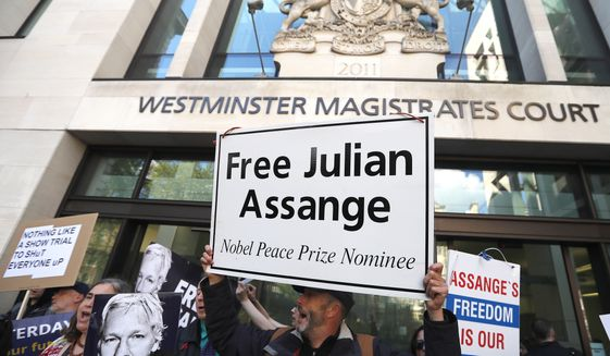 Protestors demonstrate at the entrance of Westminster Magistrates Court in London, Thursday, May 2, 2019, where WikiLeaks founder Julian Assange is expected to appear by video link from prison.  Assange is facing a court hearing over a U.S. request to extradite him for alleged computer hacking.(AP Photo/Frank Augstein)