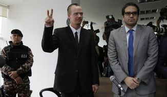 Swedish programmer Ola, center, makes a victory sign as he enters court for a hearing in which his lawyers are requesting his freedom, in Quito, Ecuador, Thursday, May 2, 2019. The government accuses Bini of being involved with two unnamed Russian hackers in a plot to blackmail Ecuadors President Lenin Moreno. (AP Photo/Dolores Ochoa)