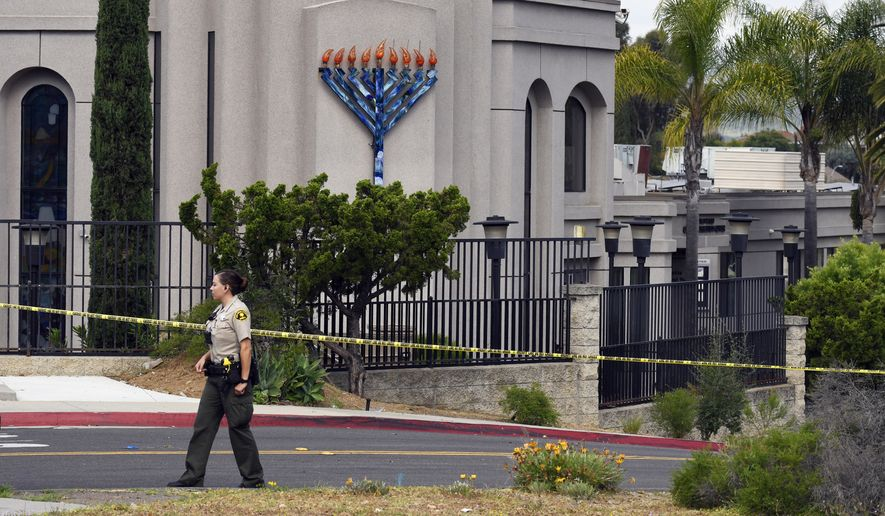 """In this Sunday, April 28, 2019 file photo, a San Diego county sheriff's deputy stands in front of the Poway Chabad Synagogue in Poway, Calif. The gunman who attacked the synagogue last week fired his semi-automatic rifle at Passover worshippers after walking through the front entrance that synagogue leaders identified last year as needing improved security. The synagogue applied for a federal grant to better protect that area. The money, $150,000, was approved in September but only arrived in late March. """"Obviously we did not have a chance to start using the funds yet,"""" Rabbi Scimcha Backman told The Associated Press. (AP Photo/Denis Poroy, File) **FILE**"""
