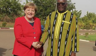 German Chancellor Angela Merkel, left, is welcome by Burkina Faso President, Roch Marc Christian Kabore, right, at the Presidential palace in Ouagadougou, Burkina Faso, Wednesday, May 1, 2019. Merkel has arrived in the West African nation of Burkina Faso. Merkel is on a three-nation tour in the region. (AP Photo/Alain Didier Compaore)