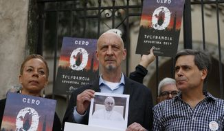 """Members of the organization called Ending Clergy Abuse, Denise Buchanan, left, and Peter Isely, center, stand with Sebastian Cuattromo, a victim of sexual abuse at a religious school when he was a youth by a teacher who was found guilty, as they stand outside a church in Buenos Aires, Argentina, Thursday, May 2, 2019. The three are demanding Pope Francis """"zero tolerance"""" regarding abuse and an end to what they see as cover ups by members of the church. (AP Photo/Natacha Pisarenko)"""