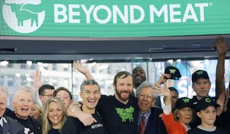 Ethan Brown, center, CEO of Beyond Meat, attends the Opening Bell ceremony with guests to celebrate the company's IPO at Nasdaq, Thursday, May 2, 2019 in New York. California-based Beyond Meat makes burgers and sausages out of pea protein and other ingredients. (AP Photo/Mark Lennihan)