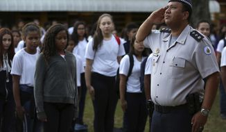 In this March 28, 2019 photo, Major Edney Freire salutes the flag during a ceremony in the main courtyard of the Ceilandia state school No. 7 in Brasilia, Brazil. The administration of President Jair Bolsonaro, a former army captain, is pushing to expand schools that are co-run by armed police to improve behavior and academic results. (AP Photo/Eraldo Peres)