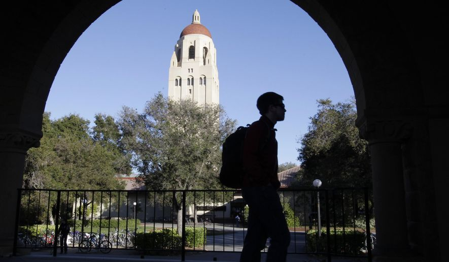 FILE - In this Wednesday, Feb. 15, 2012 file photo, a Stanford University student walks in front of Hoover Tower on the Stanford University campus in Palo Alto, Calif. A mother who says she paid the consultant at the center of the sweeping college admissions bribery scheme $6.5 million says she was duped into believing the money would help underprivileged students. A statement was released Thursday, May 2, 2019 by a Hong Kong lawyer who says he represents the mother. The statement says the consultant, Rick Singer, asked the mother to make a donation through his foundation to Stanford University after her daughter was admitted to the school.  (AP Photo/Paul Sakuma, File)