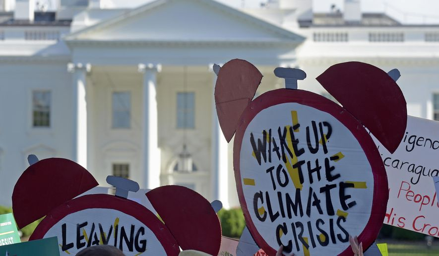 FILE- In this June 1, 2017 file photo, protesters gather outside the White House in Washington to protest President Donald Trump's decision to withdraw the Unites States from the Paris climate change accord. The Democratic-controlled House has approved legislation that would prevent President Donald Trump from following through on his pledge to withdraw the U.S. from a landmark global climate agreement. (AP Photo/Susan Walsh)