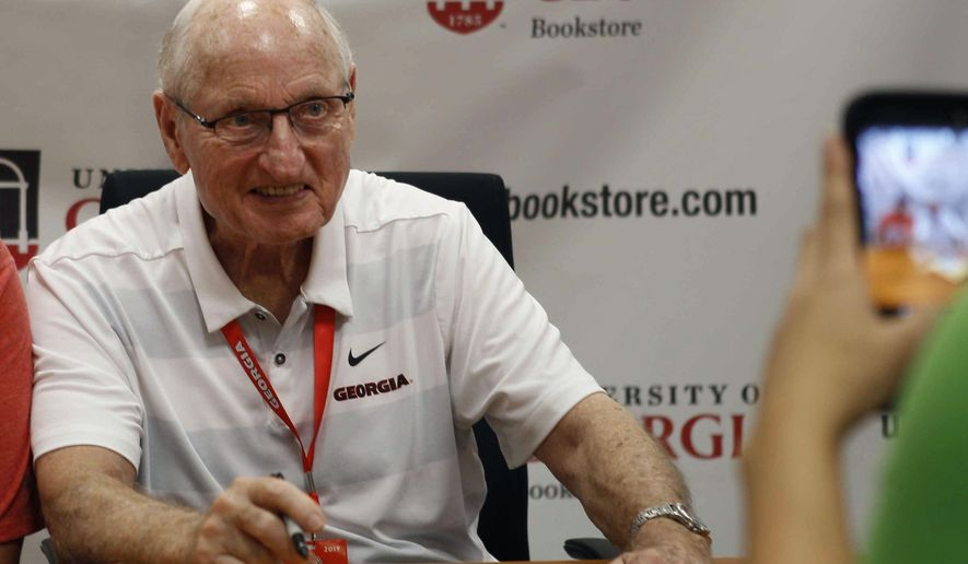 FILE - In this Sept. 29, 2018, file photo, Vince Dooley poses for a photo while signing autographs before a game between Georgia and Tennessee in Athens, Ga. Georgia is planning to honor Hall of Fame former coach Vince Dooley by naming the field at Sanford Stadium in his honor.A ceremony has been planned for Georgia's 2019 opening game on Sept. 7 against Murray State to dedicate Dooley Field at Sanford Stadium. (Jenn Finch/Athens Banner-Herald via AP, File)