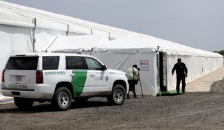 A security guard enters a new U.S. Customs and Border Protection temporary facility near the Donna International Bridge, Thursday, May 2, 2019, in Donna, Texas. Officials say the site will primarily be used as a temporary site for processing and care of unaccompanied migrant children and families and will increase the Border Patrol's capacity to process migrant families. (AP Photo/Eric Gay) ** FILE **