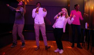 "In this March 26, 2019, file photo, from left, Zach Rowley, Bryan Cooper, Heidi Stevenson, and Liz Adeola sing at Heart & Seoul Karaoke, a new business in Salt Lake City. The state liquor commission said Tuesday, April 30 that beer will not be allowed at the Salt Lake City karaoke business or an Ogden ax-throwing venue because neither fits the definition of a ""recreational amenity,"" under a law that takes effect in mid-May. (Trent Nelson/The Salt Lake Tribune via AP, File)"
