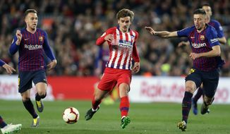 FILE - In this April 6, 2019, file photo, Atletico forward Antoine Griezmann, center, vies for the ball with Barcelona midfielder Arthur, left, and Barcelona defender Clement Lenglet, right, during a Spanish La Liga soccer match in Barcelona, Spain. Atletico Madrid will be the opponent for the Major League Soccer All-Star game this summer in Orlando. The 10-time La Liga champions are the second team from the league to play the domestic All-Stars, joining Real Madrid, the opponents in the 2017 game in Chicago. (AP Photo/Manu Fernandez, File)