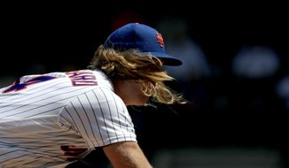 New York Mets starting pitcher Noah Syndergaard's hair flies forward as he pitches to Cincinnati Reds' Jesse Winker during the first inning of a baseball game, Thursday, May 2, 2019, in New York.(AP Photo/Julio Cortez)