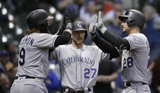 Colorado Rockies' Nolan Arenado, right, gets high-fives from Charlie Blackmon, left and Trevor Story after his three-run home run against the Milwaukee Brewers during the first inning of a baseball game Wednesday, May 1, 2019, in Milwaukee. (AP Photo/Jeffrey Phelps)
