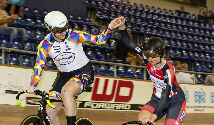 In this Oct. 13, 2018 photo provided by Craig Huffman, transgender cyclist Rachel McKinnon of Canada, left, holds hands with competitor Carolien Van Herrikhuyzen of the Netherlands during the UCI Masters Track Cycling World Championships in Carson, Calif. (Craig Huffman/Craig Huffman Photography via AP)