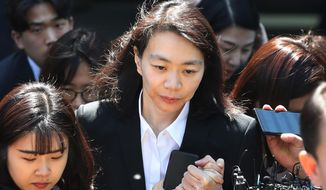 Former Korean Air executive Cho Hyun-ah, center, daughter of late Korean Air President Cho Yang-ho, leaves the Seoul Central District Court in Seoul, Thursday, May 2, 2019. Cho and his wife Lee Myung-hee, on Thursday attended the opening trial on her charges including illegal hiring of a Filipino maid. (Suh Myung-gon/Yonhap via AP)