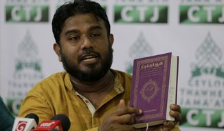 General Secretary of Ceylon Thawheed Jama'ath Abdur Razik displays a copy of Tamil language translation of holy Quran during a press conference in Colombo, Sri Lanka, Thursday, May 2, 2019. With the atmosphere still tense in Colombo, Sri Lankan Islamic group Ceylon Thawheed Jama'ath held a news conference Thursday to clarify that it was not connected to National Towheed Jamaat, despite having a similar name. (AP Photo/Eranga Jayawardena)