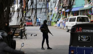 A Sri Lankan naval soldier stands guard at a road leading to a closed market on May Day in Colombo, Sri Lanka, Wednesday, May 1, 2019. Sri Lanka's major political parties called off traditional May Day rallies due to security concerns following the Easter bombings that killed more than 250 people and were claimed by militants linked to the Islamic State group. (AP Photo/Eranga Jayawardena)