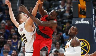 Denver Nuggets center Nikola Jokic, left, fights for control of a rebound with Portland Trail Blazers forward Al-Farouq Aminu during the first half of Game 2 of an NBA basketball second-round playoff series Wednesday, May 1, 2019, in Denver. (AP Photo/David Zalubowski)