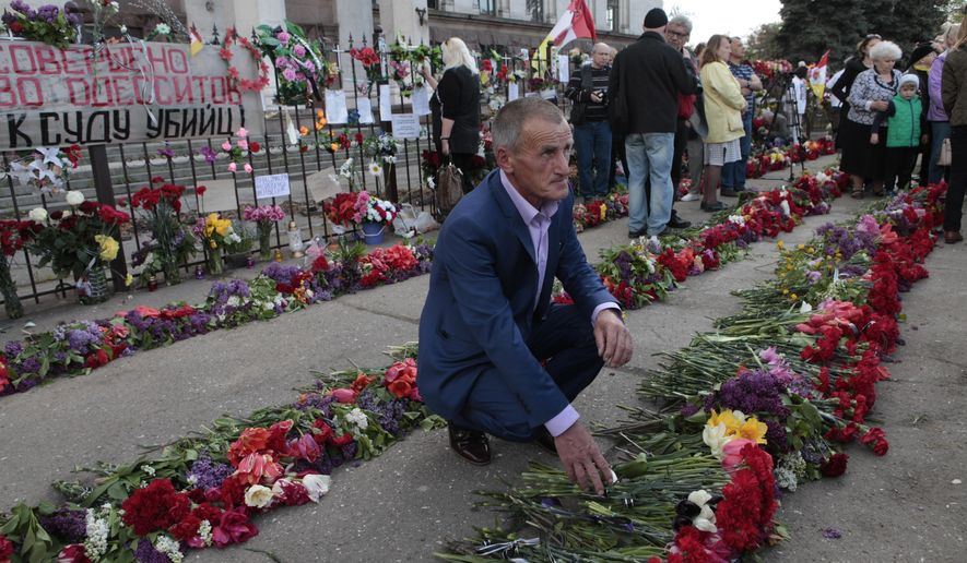 People lay flowers as they gather outside the burnt trade union building to commemorate the five-year anniversary of deadly clashes which killed dozens of demonstrators supporting Ukraine's government and pro-Russia protesters, in Odessa, Ukraine, Thursday, May 2, 2019. Five years after 48 people died in clashes in the Ukrainian city of Odessa, including dozens in a burning building, the UN human rights monitoring mission in the country is criticizing authorities for delays in prosecution and investigation of the violence. (AP Photo/Sergei Poliakov)