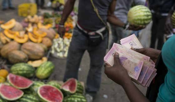 A fruit vendor counts his Bolivares in the Coche Market in Caracas, Venezuela, Thursday, May 2, 2019. Farmers truck in the produce, meat and coffee from miles around the capital to the market known for its low prices. Its customers include everybody from restaurant owners to homemakers. (AP Photo/Rodrigo Abd)