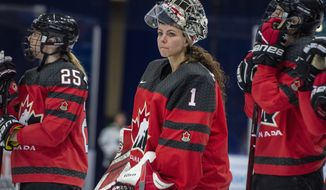 FILE - In this Nov. 10, 2018, file photo, Canada goaltender Shannon Szabados watch as U.S. players celebrate a win during the Four Nations Cup hockey gold-medal game in Saskatoon, Saskatchewan. More than 200 of the top female hockey players in the world have decided they will not play professionally in North America next season, hoping their stand leads to a single economically sustainable league. The announcement Thursday, May 2, 2019, comes after the Canadian Women's Hockey League abruptly shut down as of Wednesday, leaving the five-team, U.S.-based National Women's Hockey League as the only pro league in North America. The group of players, led by American stars Hilary Knight and Kendall Coyne Schofield and Canadian goaltender Shannon Szabados, hopes their move eventually pushes the NHL to start its own women's hockey league as the NBA did with the WNBA. (Liam Richards/The Canadian Press via AP) ** FILE **