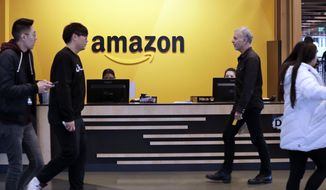 FILE - In this Nov. 13, 2018 file photo, employees walk through a lobby at Amazon's headquarters in Seattle. On Friday, May 3, 2019, shares in Amazon are moving higher after billionaire investor Warren Buffett said his firm has been buying the online retailer. (AP Photo/Elaine Thompson)