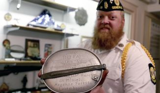 In this Monday, April 22, 2019 photo, Matthew Lutz holds an artifact at the Geneva American Legion Post #75 in Geneva, Ill. Lutz Marine, a Marine veteran is trying to locate, repair and catalog everything at an American Legion Post in northern Illinois ahead of its 100-year anniversary. (Patrick Kunzer/Daily Herald via AP)