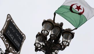 A demonstrators waves an Algerian flag during a protest in Algiers, Algeria, Friday, May 3, 2019. Tens of thousands of Algerians protested for an 11th straight week on Friday to pressure those in power to leave, a month after long-time President Abdelaziz Bouteflika was forced to resign. (AP Photo/Toufik Doudou)