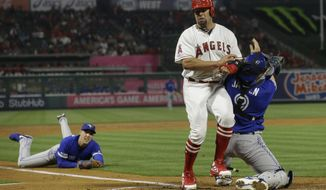 Toronto Blue Jays catcher Danny Jansen, right, tags out Los Angeles Angels' Albert Pujols at the plate, who tried to score on a ball hit by Justin Bour, as starting pitcher Aaron Sanchez, left, watches after throwing the ball to Jansen during the third inning of a baseball game in Anaheim, Calif., Thursday, May 2, 2019. (AP Photo/Chris Carlson)