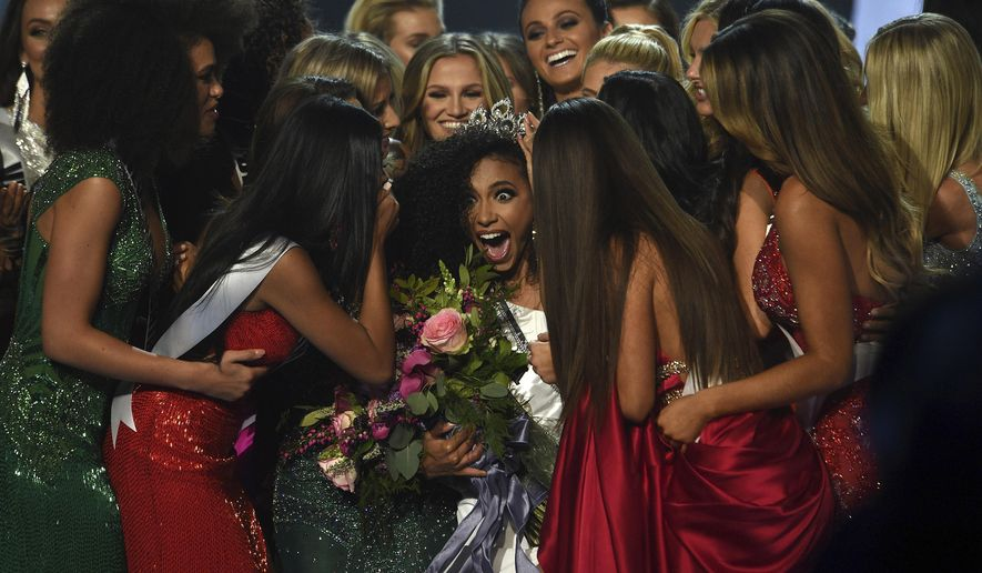 Miss North Carolina Cheslie Kryst, center, gets mobbed by her fellow contestants after winning the 2019 Miss USA final competition in the Grand Theatre in the Grand Sierra Resort in Reno, Nev., on Thursday, May 2, 2019. Kryst, a 27-year-old lawyer from North Carolina who represents some prison inmates for free, won the 2019 Miss USA title Thursday night in a diverse field that included teachers, nurses and members of the military. (Jason Bean/The Reno Gazette-Journal via AP)