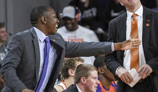 In this February, 2019 photo, Clemson assistant coach Steve Smith, left, gestures as head coach Brad Brownell, right, looks up, during an NCAA college basketball game in Clemson, S.C. Clemson has parted ways Smith on Friday, May 3, 2019, after his voice was heard on a federal wiretap involving defendant Christian Dawkins on the ongoing trial into college corruption. (Ken Ruinard/The Independent-Mail via AP)
