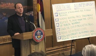 Colorado Gov. Jared Polis touts the Democrat-led legislature's accomplishments in tackling health care costs at a state Capitol briefing on Friday, May 3, 2019, in Denver. Polis spoke on the final day of Colorado's four-month 2019 session. (AP Photo/Jim Anderson)