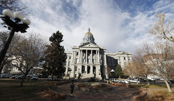 FILE--In this Tuesday, Nov. 27, 2018, photograph, clouds build over the State Capitol in downtown Denver. Colorado lawmakers close their 2019 session Friday, May 3, 2019. (AP Photo/David Zalubowski, File)
