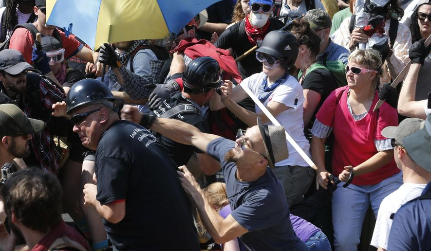 In this Aug. 12, 2017 file photo, white nationalist demonstrators clash with counter demonstrators at the entrance to Lee Park in Charlottesville, Va. (AP Photo/Steve Helber, File)