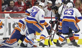 Carolina Hurricanes' Sebastian Aho scores against New York Islanders goalie Robin Lehner while Islanders' Scott Mayfield (24) and Casey Cizikas (53) defend with Adam Pelech during the first period of Game 4 of an NHL hockey second-round playoff series in Raleigh, N.C., Friday, May 3, 2019. (AP Photo/Gerry Broome)