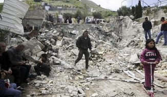 """FILE - In this April 17, 2019 file photo, Palestinians watch a family house destroyed by Israeli authorities in east Jerusalem's neighborhood of Silwan. Scores of Palestinian-owned residences in east Jerusalem now face demolition by Israeli authorities after the Supreme Court dismissed residents' appeal on the grounds that the houses were built illegally in a city park. Activists and Palestinian residents of the so-called """"Peace Forest"""" say the case highlights the city's discriminatory housing policies, as construction by a nationalist Jewish organization accelerates in the same park. (AP Photo/Mahmoud Illean, File)"""