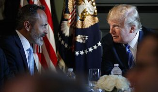 FILE - In this Aug. 9, 2018 file photo, President Donald Trump talks with Kentucky Gov. Matt Bevin during a meeting with state leaders about prison reform at Trump National Golf Club in Bedminster, N.J. Bevin plays up his close ties with Trump and boasts about the state's economy in his first TV ad of his reelection campaign. The Republican governor's campaign team said Friday, May 3, 2019, the ad will air during the Kentucky Derby. (AP Photo/Carolyn Kaster, File)
