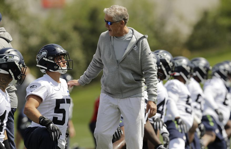 Seattle Seahawks coach Pete Carroll, center, talks with rookie linebacker Cody Barton, left, during NFL football rookie minicamp Friday, May 3, 2019, in Renton, Wash. (AP Photo/Ted S. Warren) ** FILE **