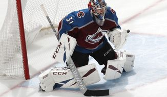 Colorado Avalanche goaltender Philipp Grubauer deflects a San Jose Sharks shot during the first period of Game 4 of an NHL hockey second-round playoff series Thursday, May 2, 2019, in Denver. (AP Photo/David Zalubowski)